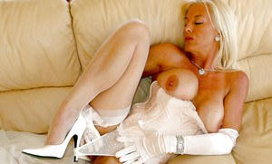 Mature blonde in stockings uncovering her boobs and taking off her panties