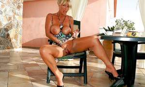 Tempting mature lady uncovering her big bosoms and taking off her panties