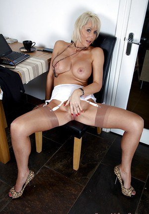 Mature office assistant Jan exposing her long legs in stockings