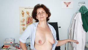 Lusty mature nurse in glasses showcasing her flabby tits and pink twat