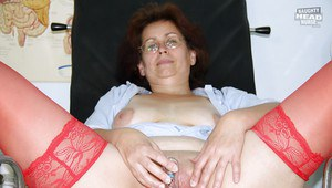 Horny mature lady in glasses stuffing her twat with a dildo and speculum