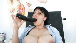 Full-figured mature brunette playing with her sex toys in gyno office