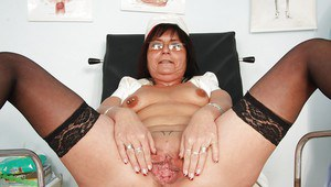 Mature lady in glasses taking off her panties and exposing her pierced cunt