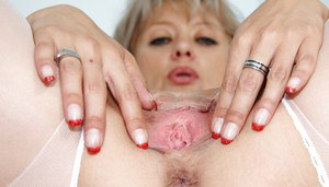 Lusty mature nurse in stockings revealing her shaved pink twat