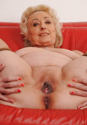 Naughty granny with massive flabby boobs stripping and spreading her legs