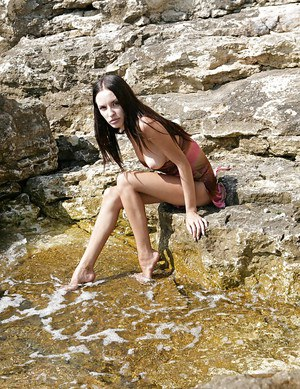 Graceful brunette with long legs slipping off her clothes outdoor