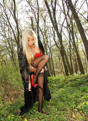 Seductive blonde babe in stockings showcasing her goods outdoor
