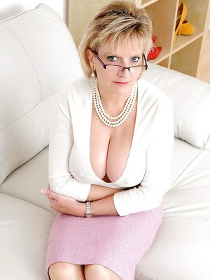 Big busted mature lady in glasses slips off her skirt and exposes her ass