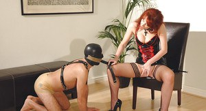 Mature fetish lady in latex dress torturing her male pet's dick