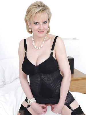 Busty mature lady in lingerie and stockings flashing her juicy cunt