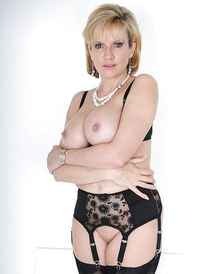 Tempting mature blonde in stockings and lingerie exposes her jugs and ass
