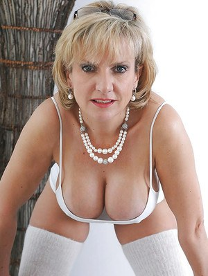 Leggy mature lady posing in white lingerie and cotton stockings