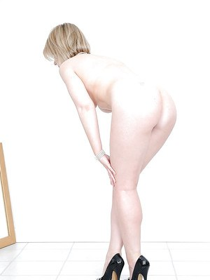 Lusty mature blonde with round boobs and ample ass posing nude