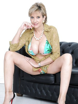 Leggy mature blonde uncovering her round tatas and inviting twat