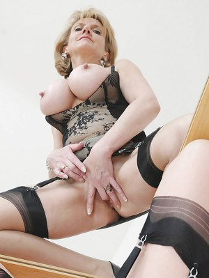 Well-stacked mature lady in lingerie and stockings fingering her twat
