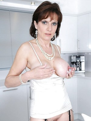 Barely clothed mature fetish lady revealing her jugs and teasing her nipples