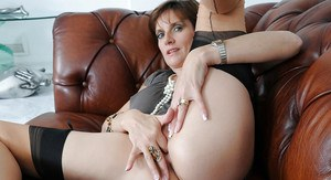 Lustful mature lady in stockings fingering her pink twat