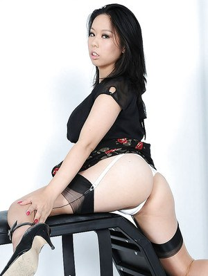 Lusty asian lady in stockings lifts up her dress and exposes her ample ass