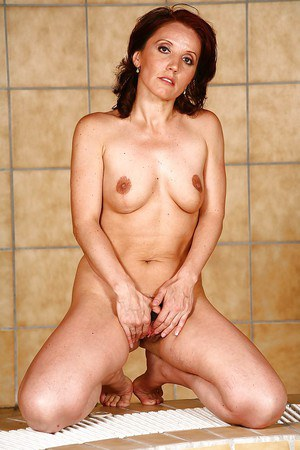 Attractive mature brunette gets rid of her clothes by the pool
