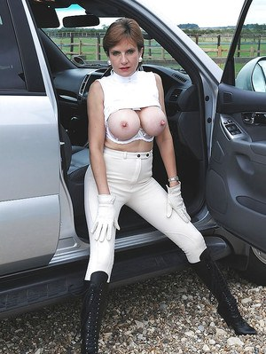 Mature fetish lady in high-heeled boots uncovers her big tits outdoor