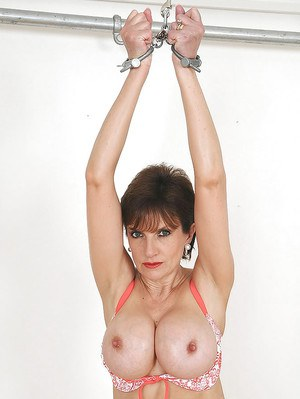Handcuffed mature fetish lady in lingerie revealing her big jugs