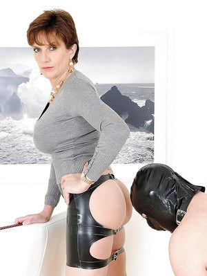 Mature femdom in provocative skirt has some fun with her masked male pet