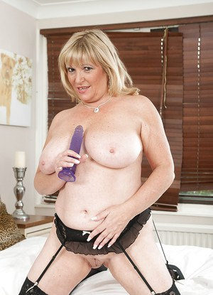 Fatty mature blonde stripping and stuffing her cunt with a vibrator