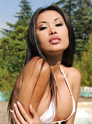 Graceful asian vixen in jeans shorts showcasing her goods by the pool