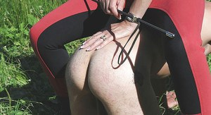 Topless mature femdom has some fun with her male pet outdoor