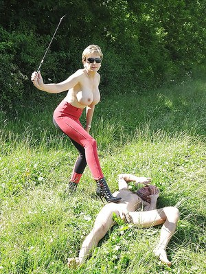 Topless femdom in sunglasses torturing her male pet outdoor