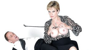 Mature femdom reveals her big tits while torturing her male pet