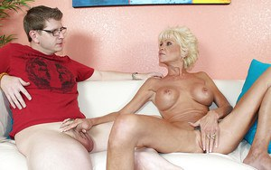 Sassy mature blonde with big tits strips down and gives a handjob