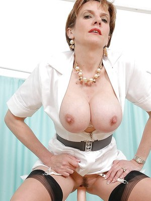 Mature fetish lady reveals her big tits while riding on a fucking machine