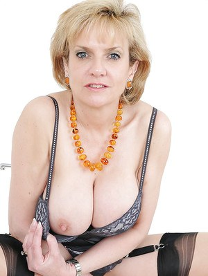 Barely clothed mature blonde in stockings revealing her round boobs