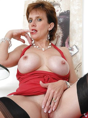 Barely clothed mature lady spreading her legs and fingering her gash