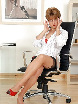 Mature office lady in glasses posing barely clothed at her work place