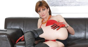 Barely clothed mature vixen in thigh boots demonstrating her sexy curves