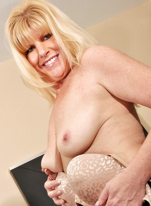 Mature lassie in stockings stripping down and playing with a dildo