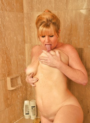 Chesty mature lady taking shower and fingering her hungry twat