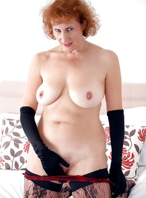 Curly-haired mature lady with chubby curves getting rid of her lingerie