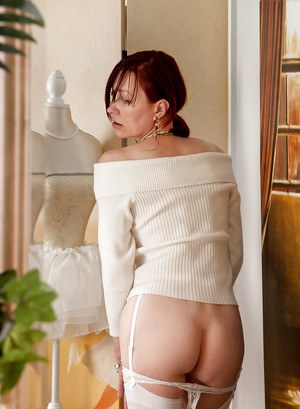 Naughty mature lady getting rid of her clothes and caressing herself