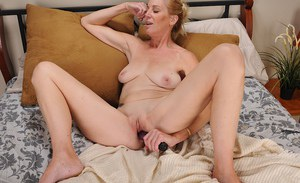 Mature lady with big saggy tits pleasing her shaved twat with a vibrator