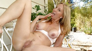 Sassy mature blonde getting bottomless and fingering her cunt outdoor
