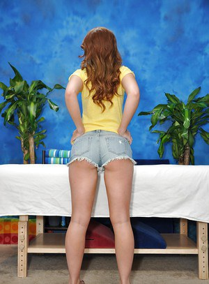 Teenage redhead sweetie in daisy duck shorts undressing in the massage parlor
