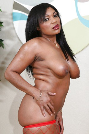 Ebony lassie in fishnet stockings uncovering her oiled up curves