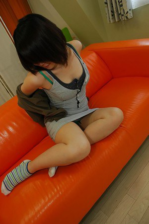 Smiley asian teen Maki Yoshikawa undressing and posing nude on the couch