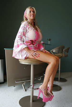 Stunning mature blonde on high heels revealing her big jugs and trimmed pussy