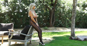 Desirable housewife with big breasts posing in erotic nylon suit outdoor