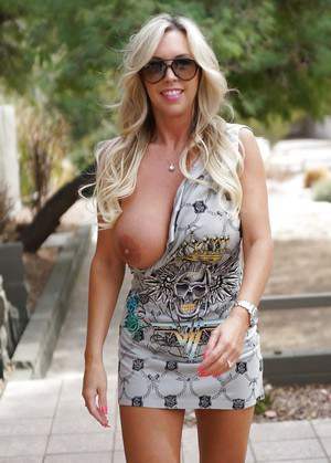 Naughty housewife in sunglasses uncovering her amazing big tits outdoor
