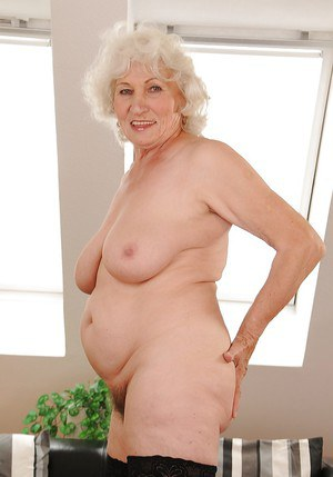 Salacious granny in stockings undressing and exposing her shaggy twat